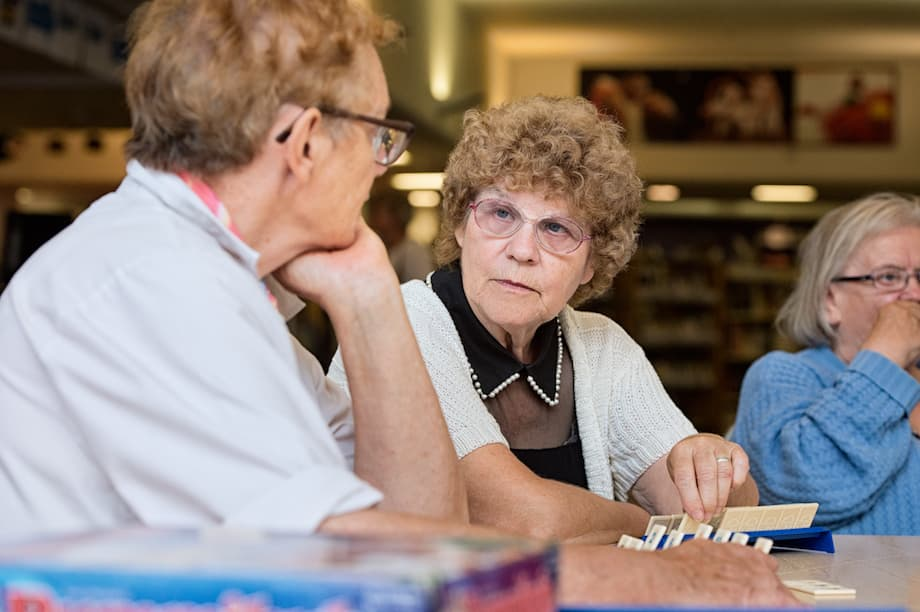 Two women playing Scrabble in a library.