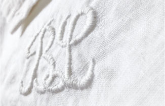 Une couturière brode du textile