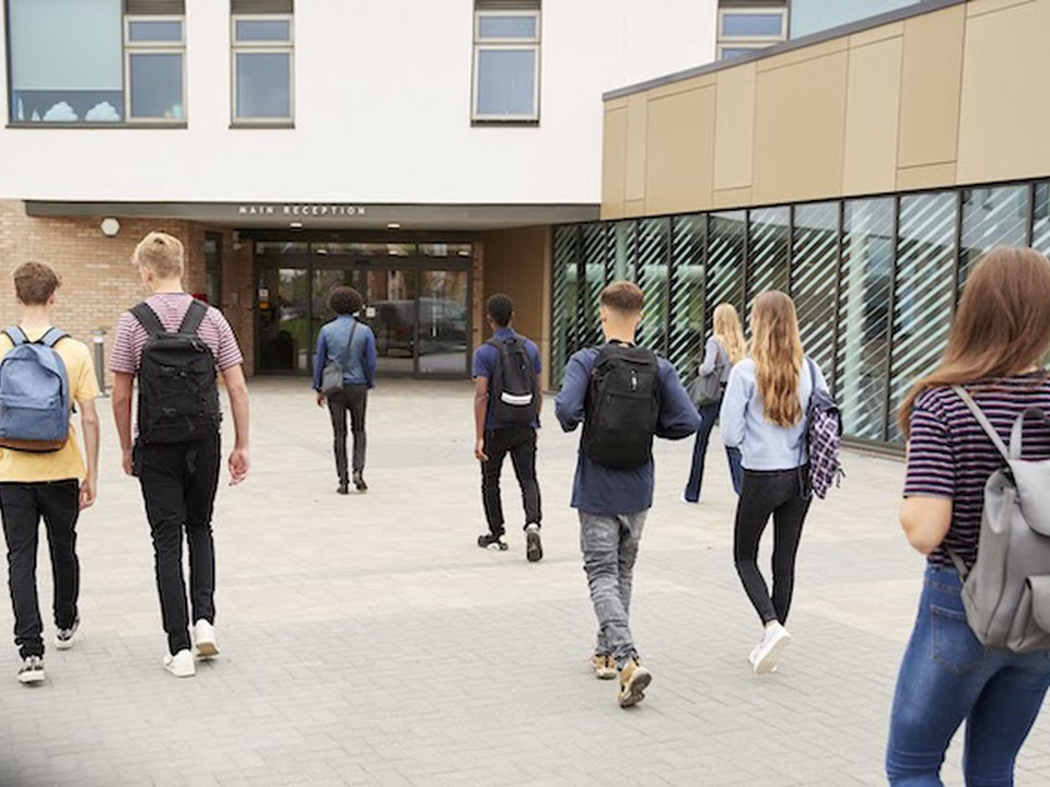 High school students walk into a school building.