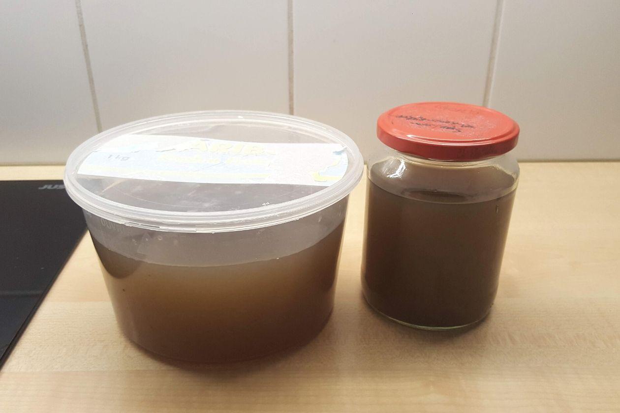 Die abgefüllte Zero Waste Gemüsebrühe in einer alten Haribo-Box und einem Schraubglas.