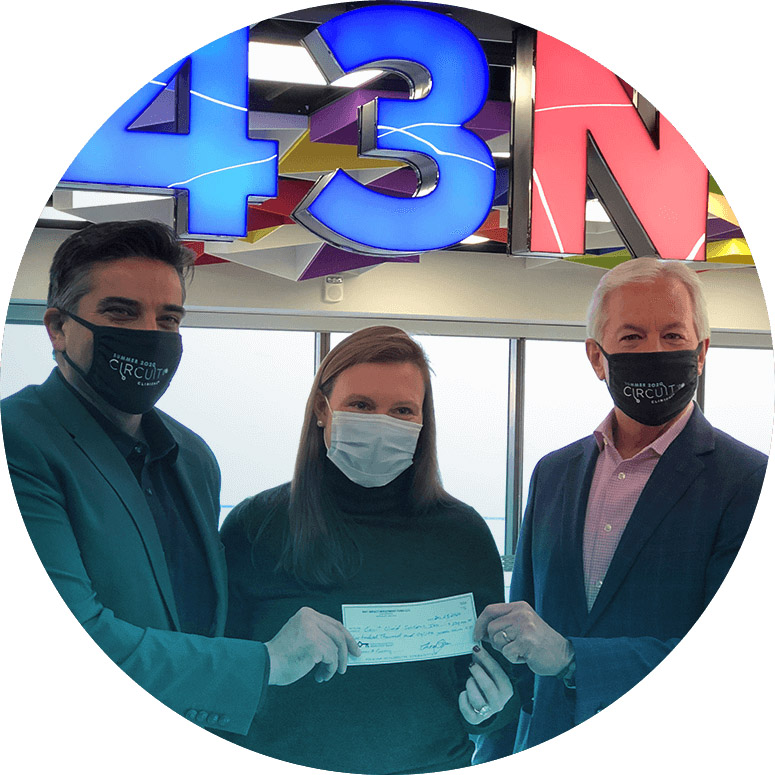 Three people holding a check