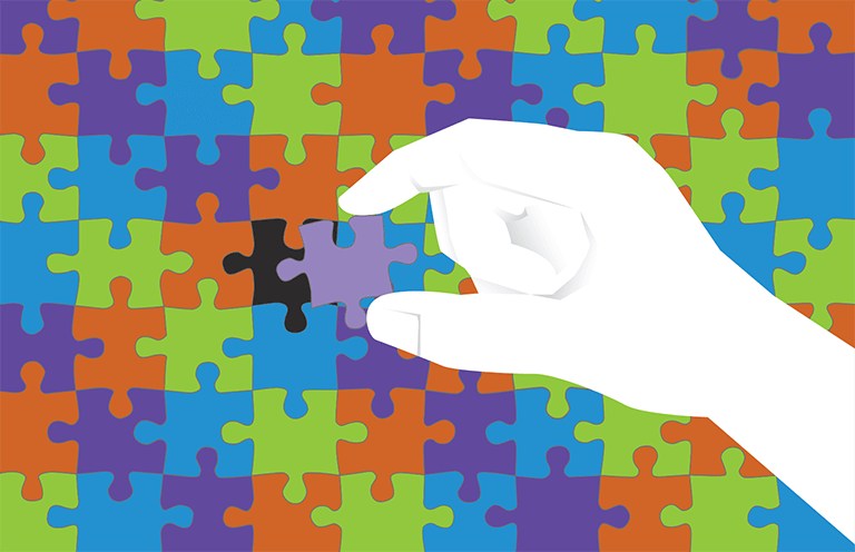 A puzzle with multicolored pieces, and a hand placing the final piece in place
