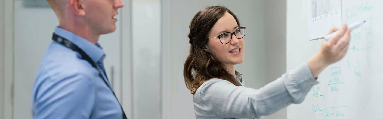 Beraterin an Whiteboard berät Kunden