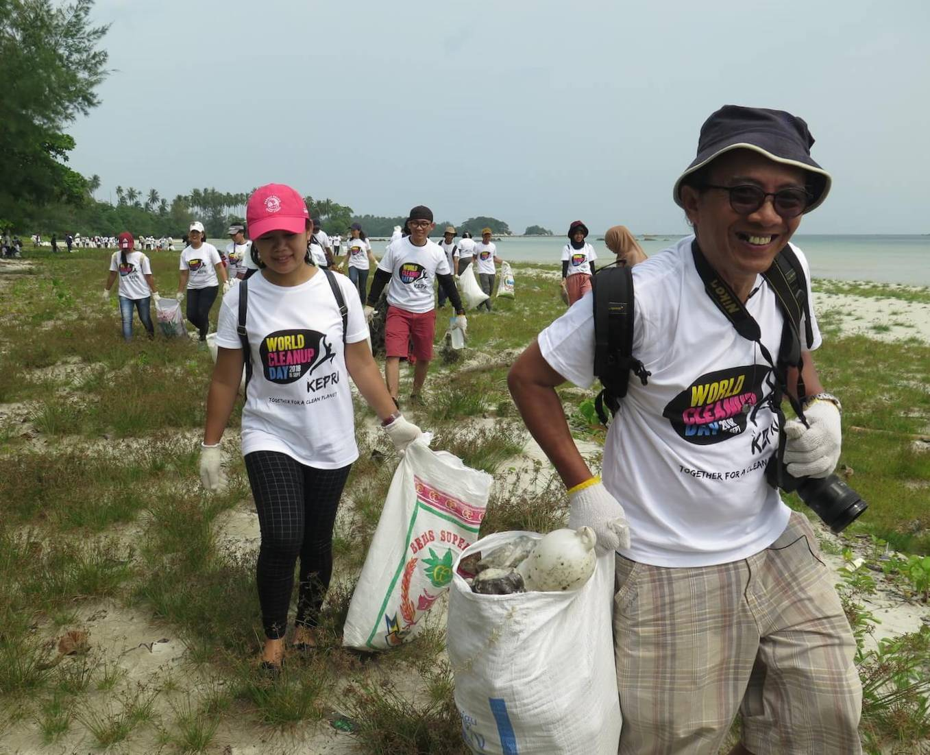 Indonesian man smiling and holding a bag full of plastic waste, a woman behind her and many people in the background, all holding bags with garbage and walking on the beach.