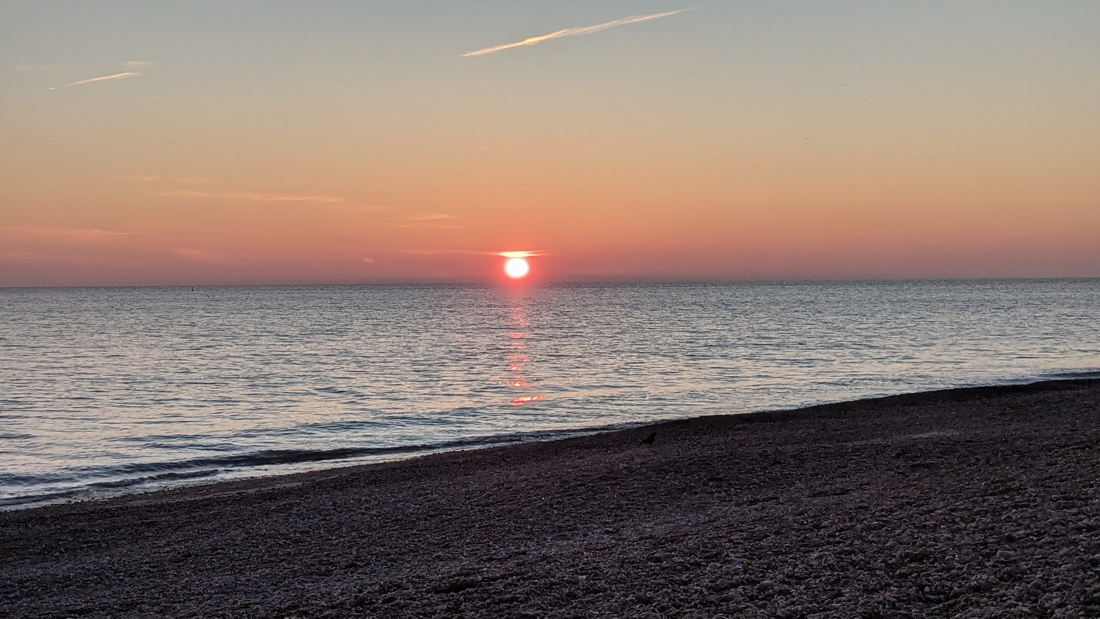 Sun setting over the sea with shingle in the foreground and the town of Worthing in the distance.