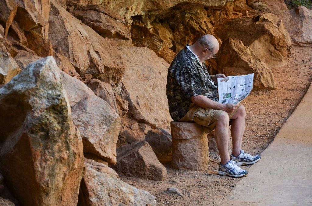old man reading a map at a tourist site