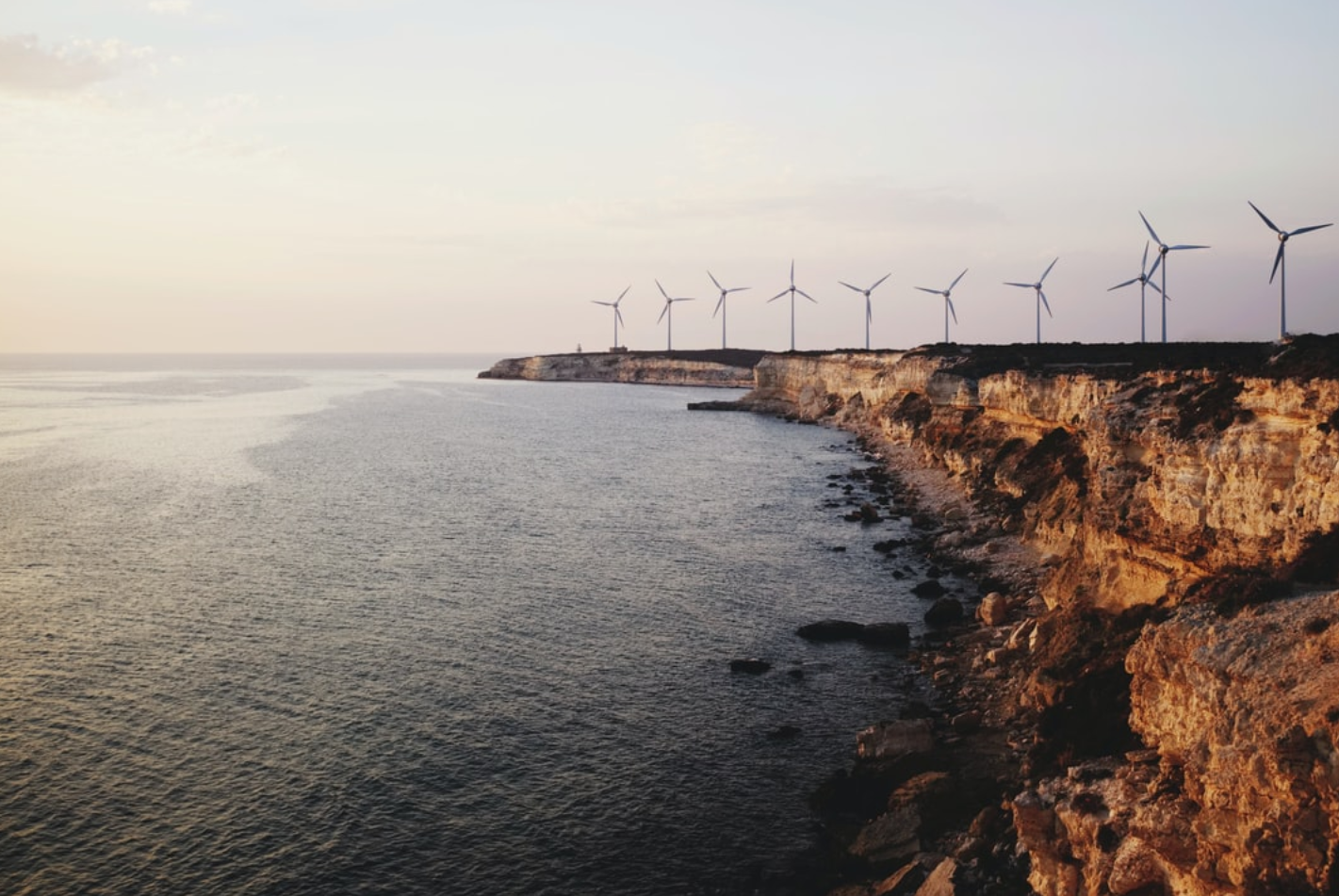 Windmills lined up on a rocky coast