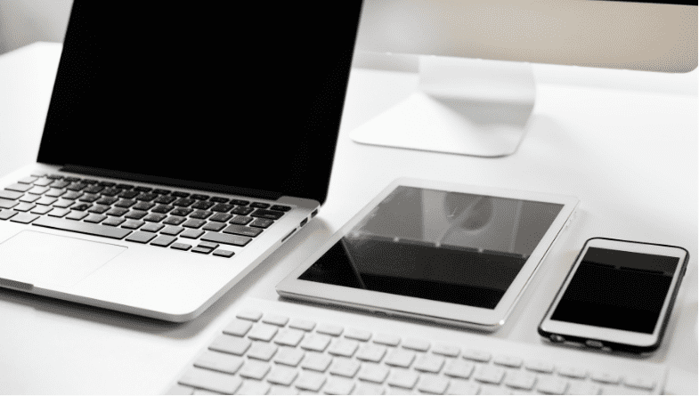 Laptop, iPhone, iPad and keyboard lie on white desk for research for 5 reasons why cloud -based inventory systems with Futrli are best for online selling for business owners #onlineselling