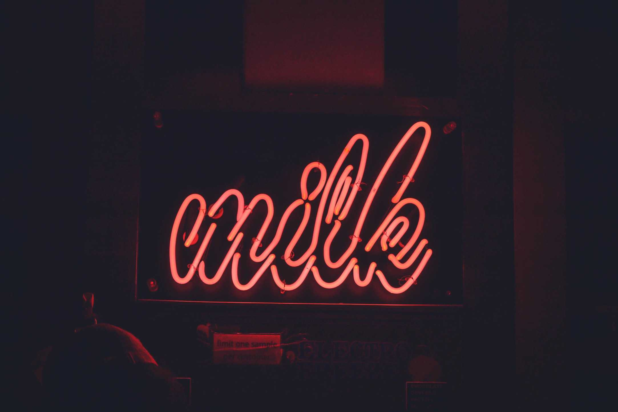 Neon sign showing the text- 'milk'. The rise of plant-based milks are leading many to re-define what the word milk means