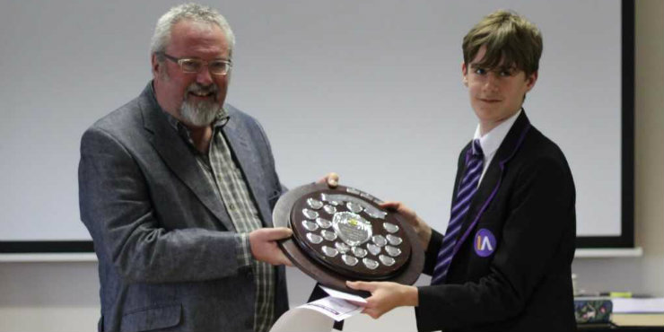 Josh Mayhew receives the Book Mastermind trophy from Suffolk Libraries Board chair Tony Brown