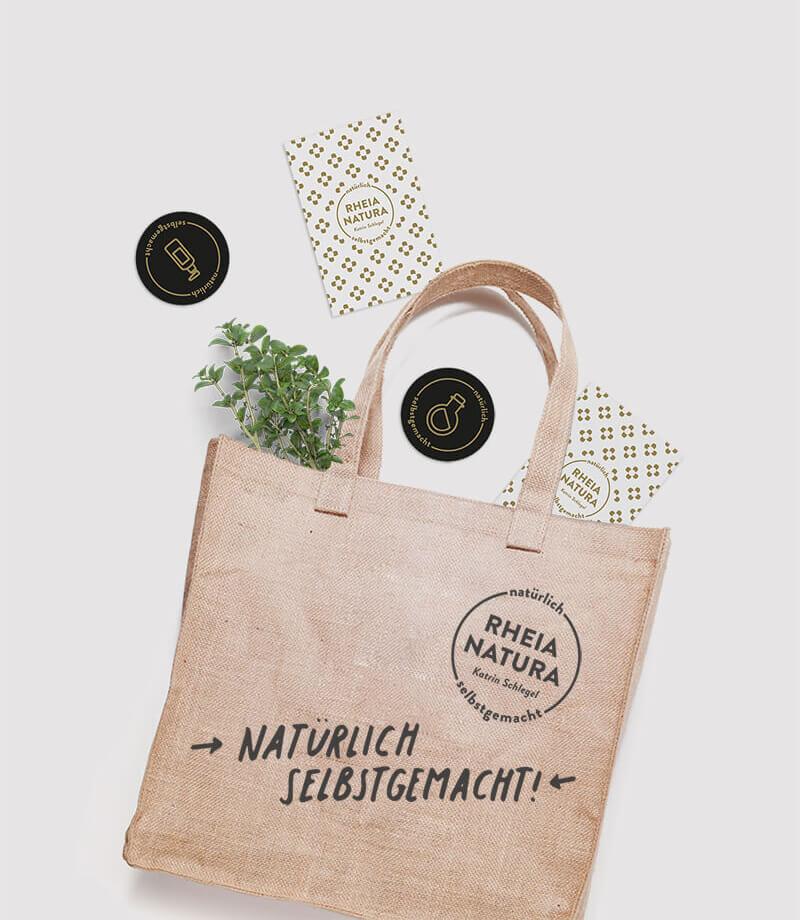 Buttons, Visitenkarten und Tasche im Corporate Design von Rheia Natura
