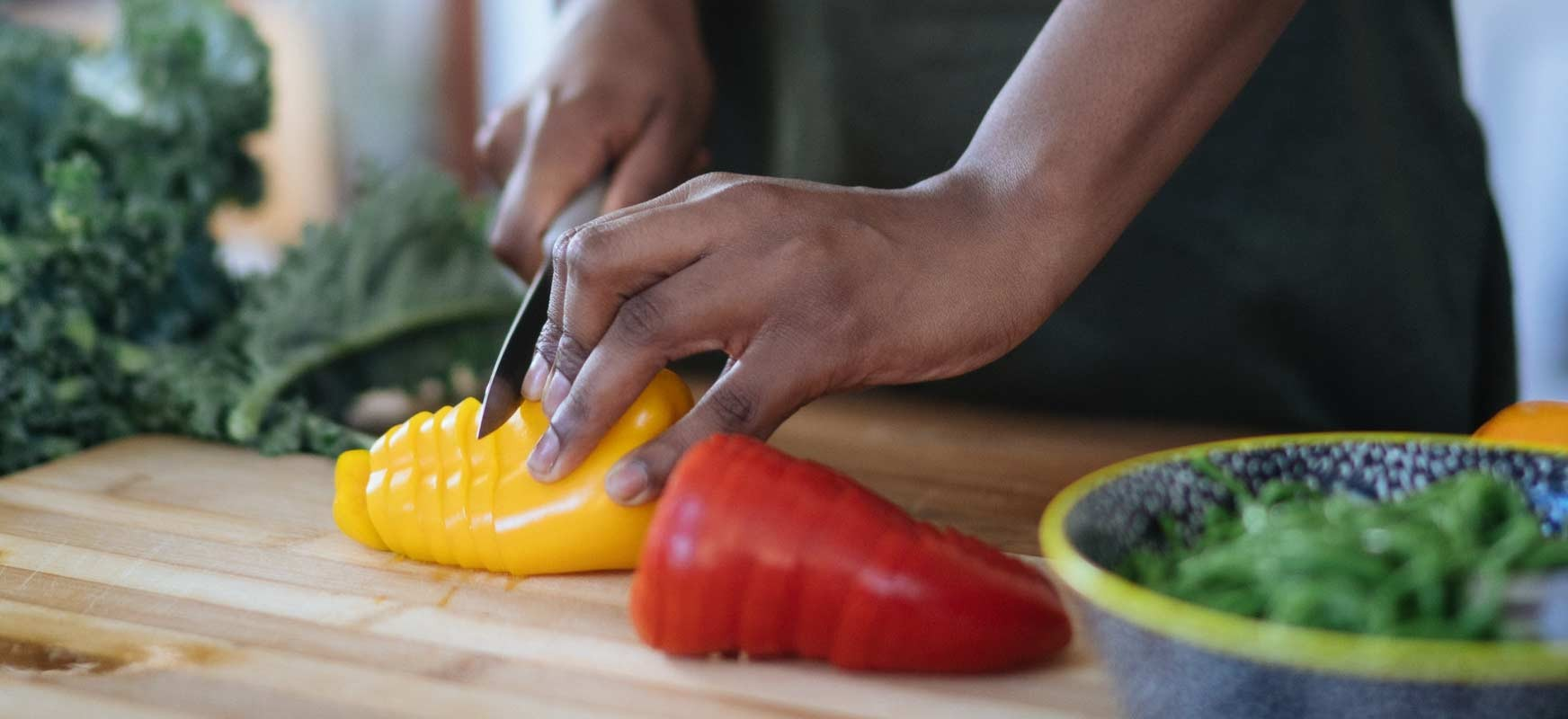 A person cuts up bell peppers for a salad to avoid food waste