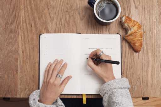 Woman business owner writes a to-do list in notepad/journal/planner with a pen for 2020. She also has a coffee and a croissant
