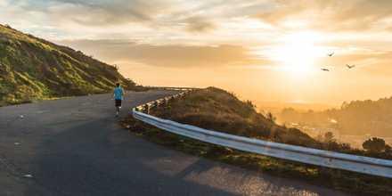 Runner towards sunrise up a hill
