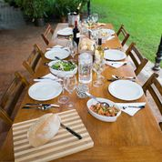 A long outdoor dining table set with a lunch spread for six places