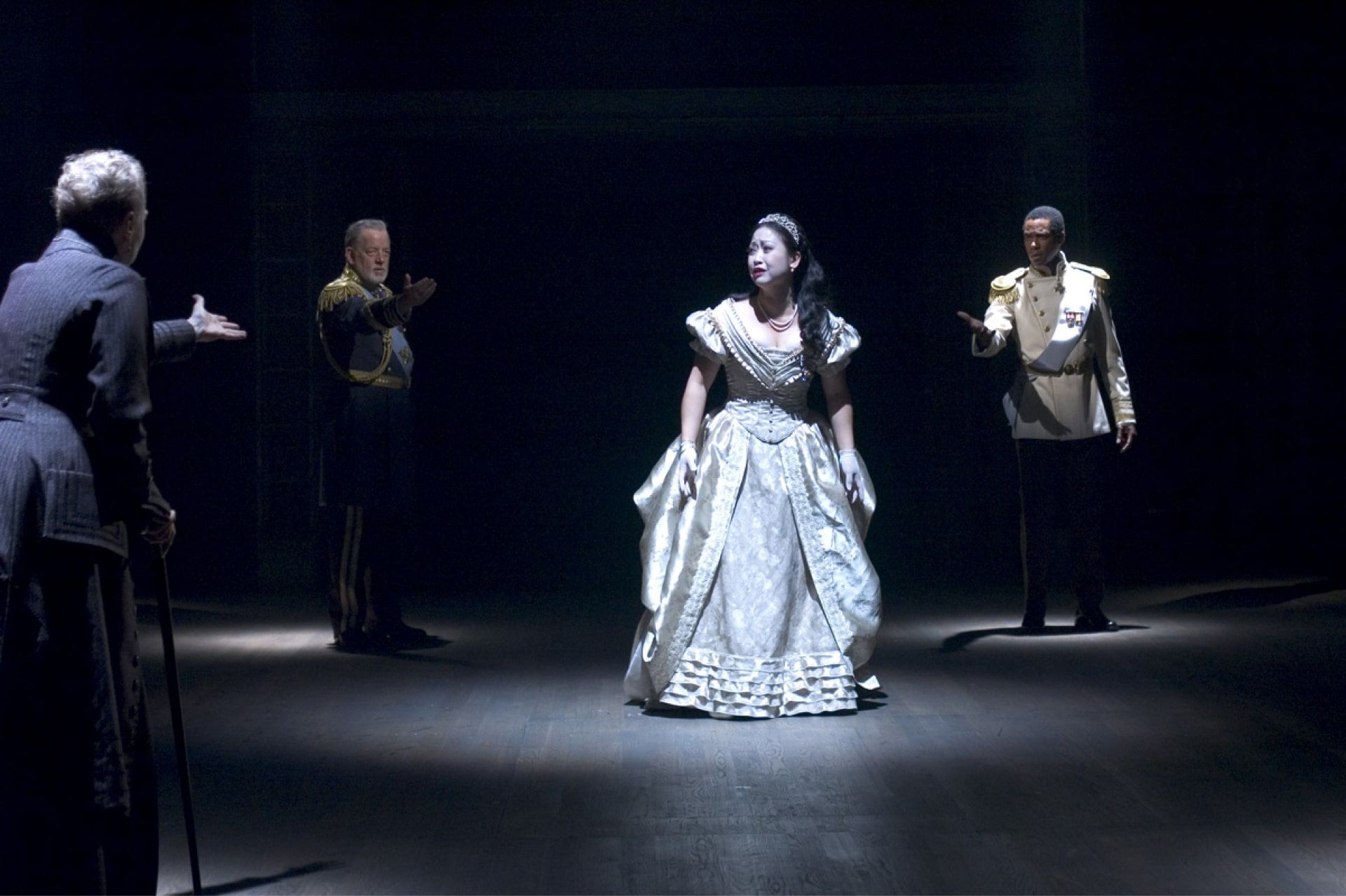Woman in white gown stands in spotlight surrounded by three men other characters.
