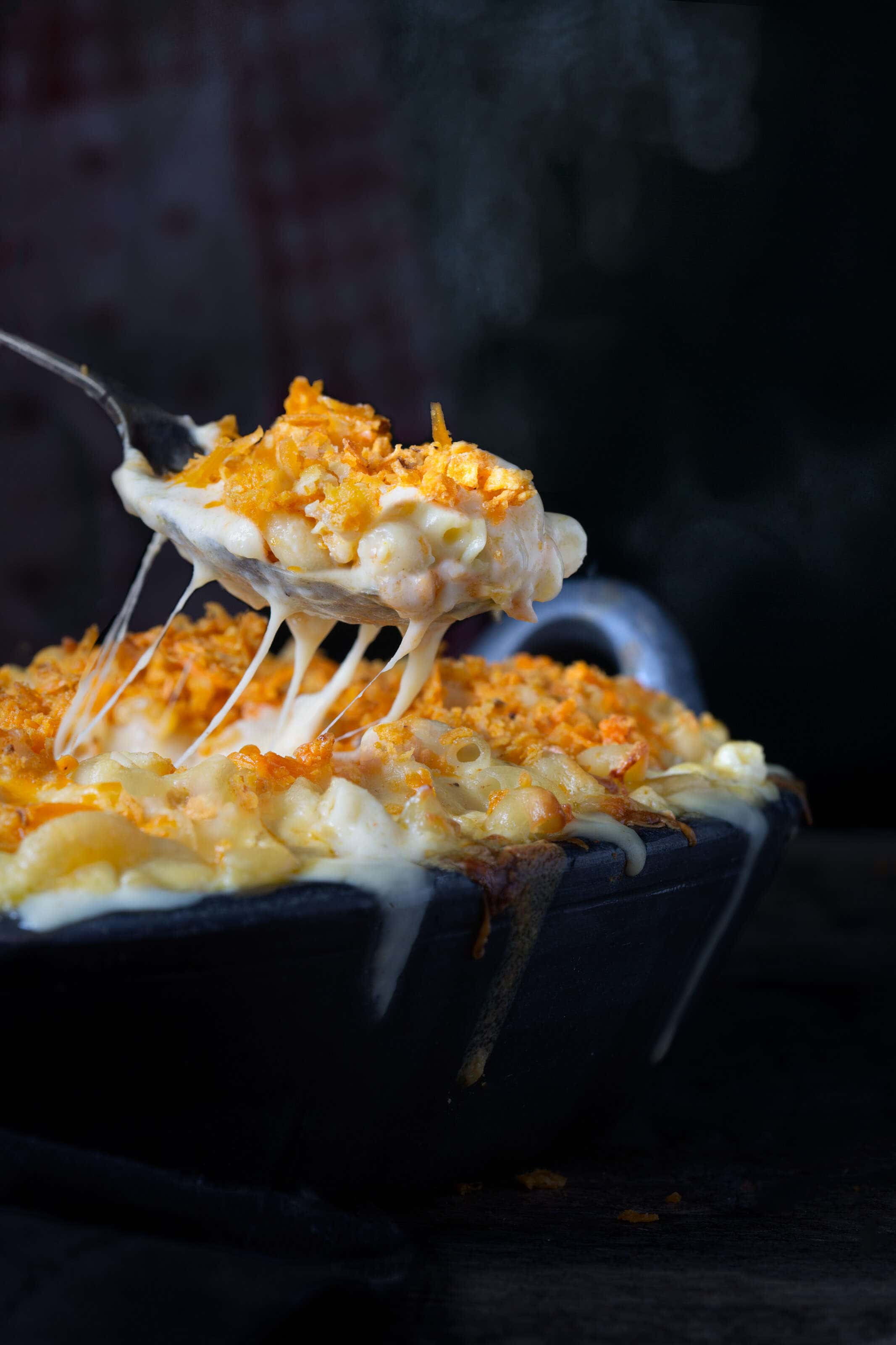Hot macaroni cheese being served with a spoon with steam rising from it.