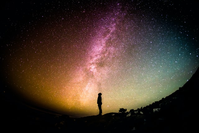 Man in sillhoute staring at the milky way with beautiful colors