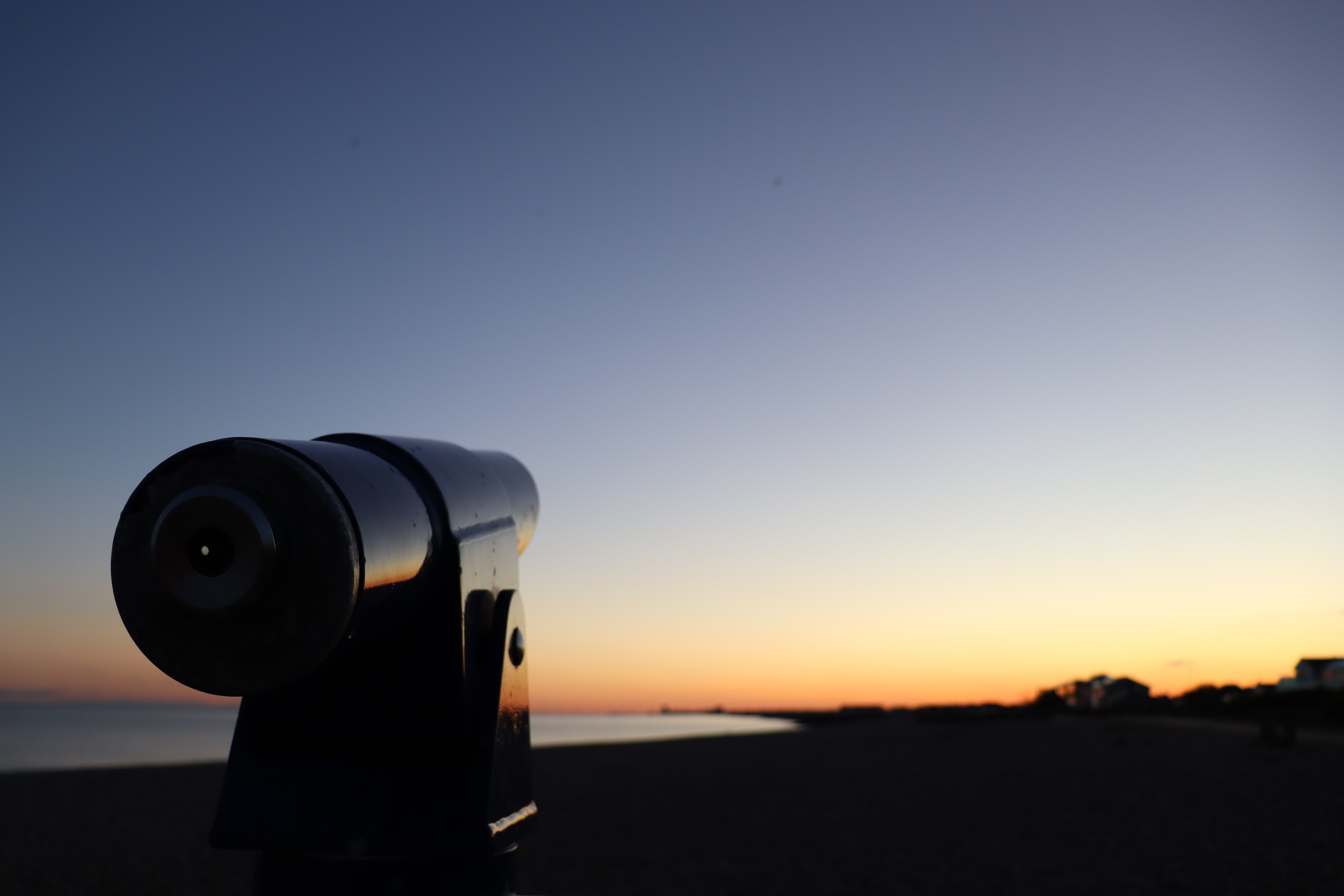 A fixed telescope pointing towards the out of focus sunset over the sea.