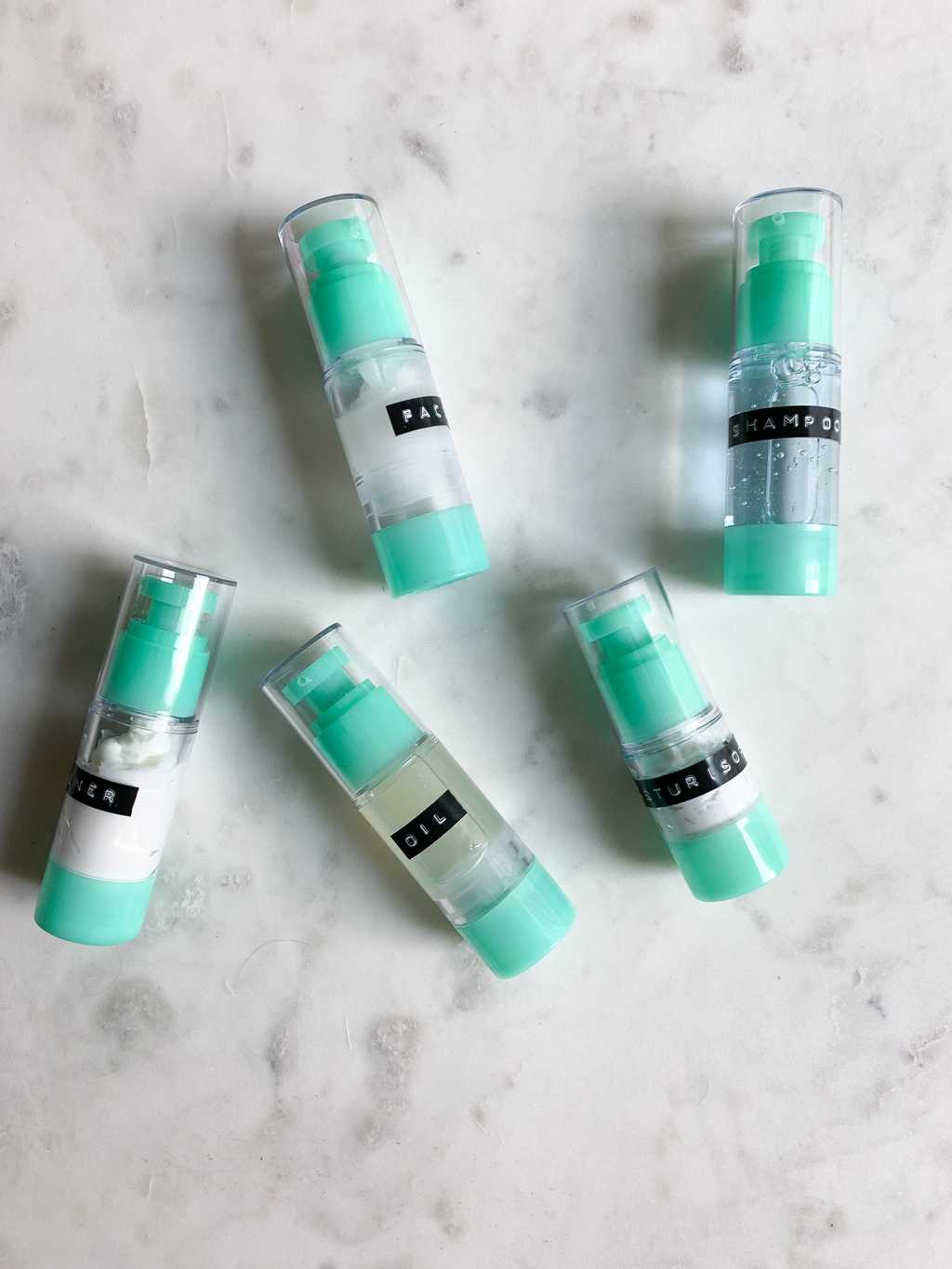 Aqua and clear pump bottles on marble backdrop