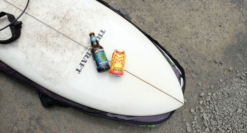 Outburst Bottle and Blazing Bright can on a surfboard in the sand