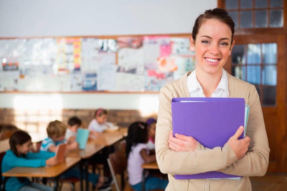 A woman, smiling and holding a purple folder. There's a children's classroom on the background