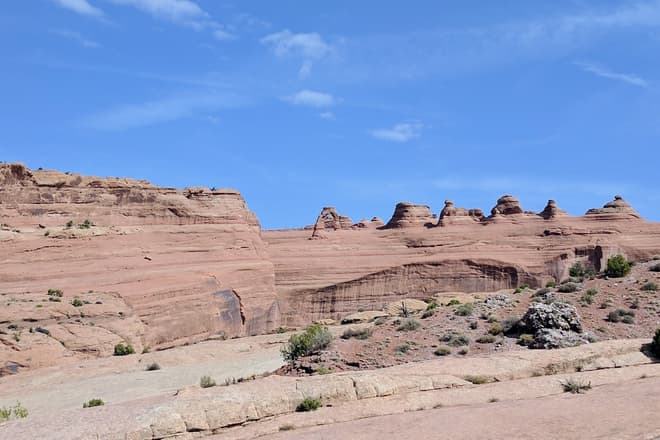 A distant view of Delicate Arch, which sits atop a large, wide sandstone fin. Scores of hikers, almost too small to see at this distance, cluster around it.