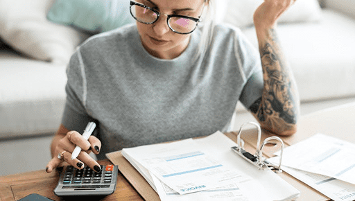 A woman in black glasses and a grey top sat at a desk with lots of papers and a calculator in front of her and tattoos on her arm.