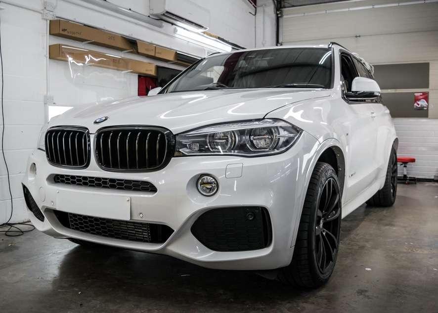 White BMW X5 during window tinting