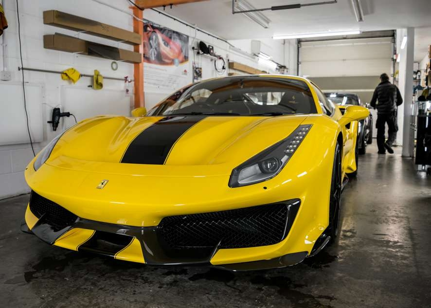 Car in studio/garage yellow Ferrari 488 Pista after paintwork protection, paint protection film (PPF) and ceramic coating application.