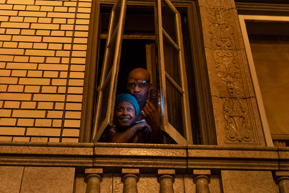 30-year residents of Adams Point pose for a photo in the window of the apartment during the 'Justice for Jacob' protest in Oakland, Calif., August 26, 2020. The couple said they were unable to sleep due to noise as protesters were dispersed by police.