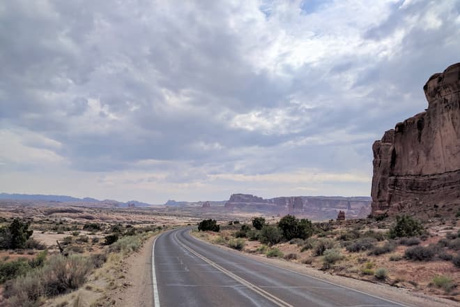 Looking south back along the main road into Arches National Park. In the distance, massive fins of red sandstone.