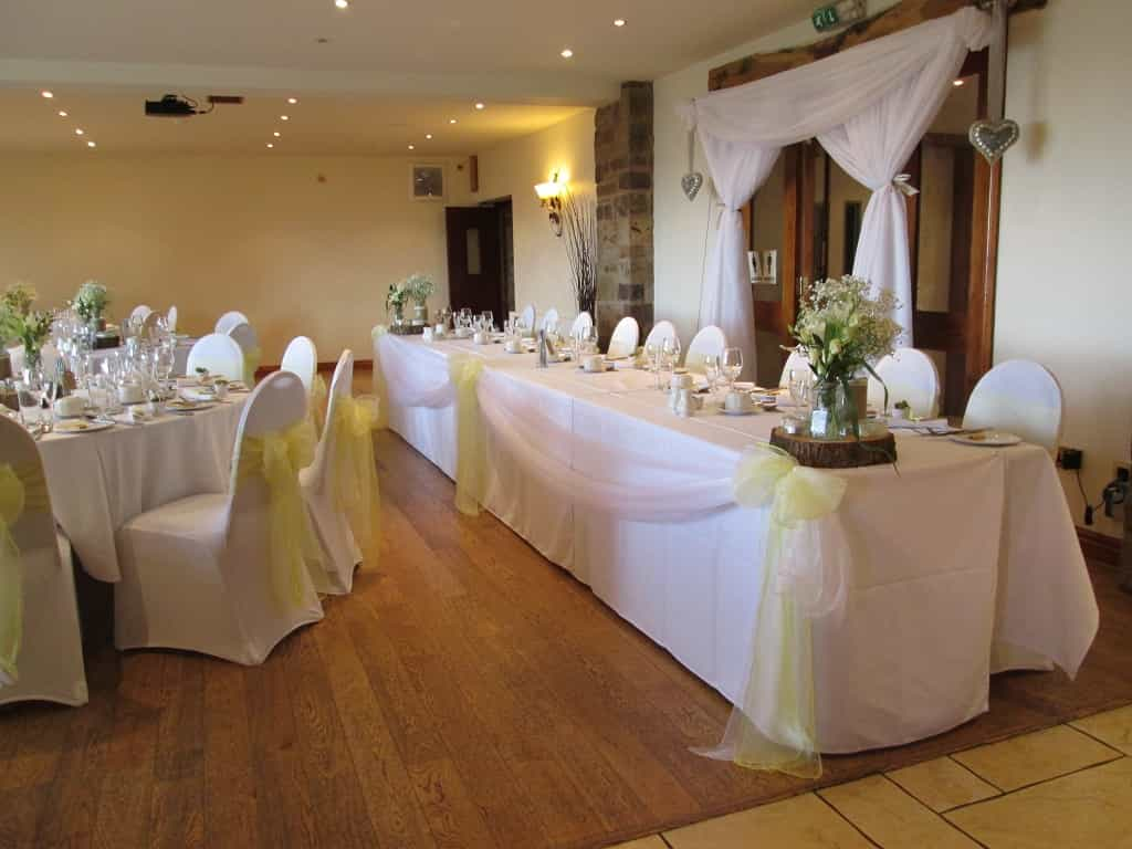 Wedding breakfast with white table linen and chair covers with ivory sashes