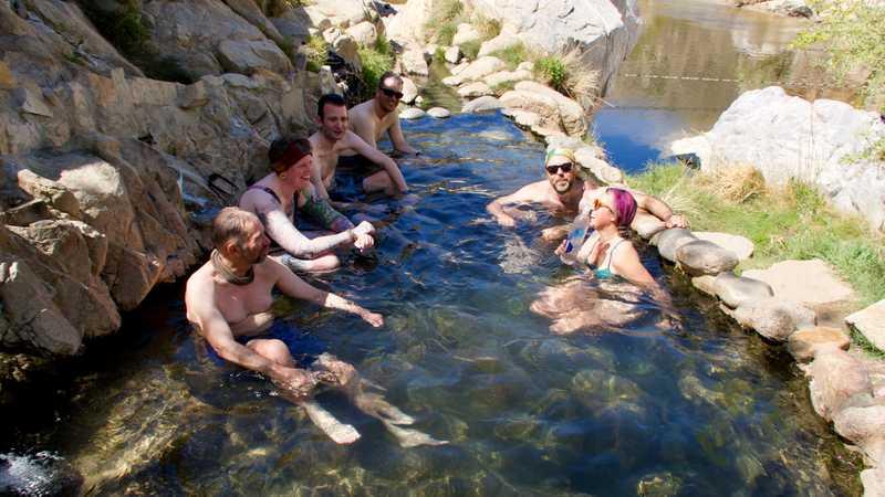 Tramily sitting in hot springs pool