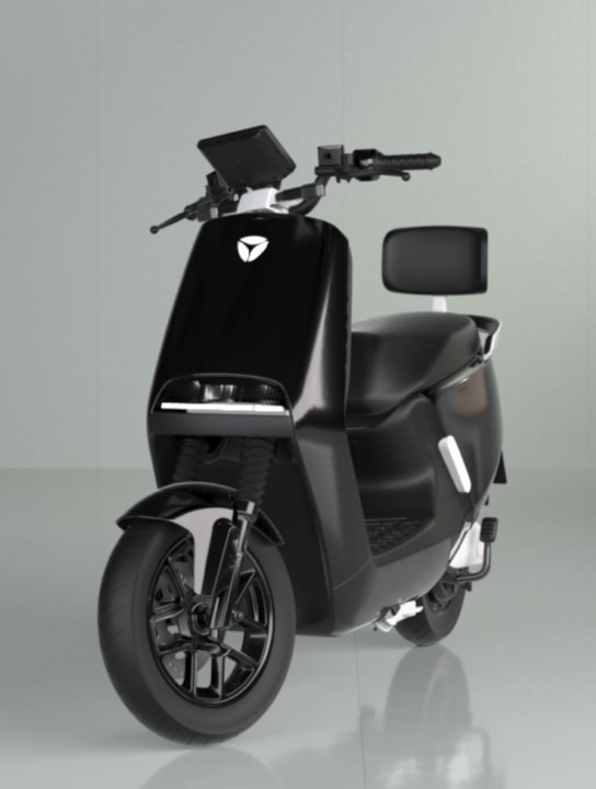 A black electric scooter branded with the Yadea logo in a romantically lit grey room.
