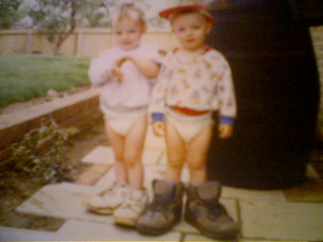 Picture of Luke and Ellis as twins, wearing rather large shoes.