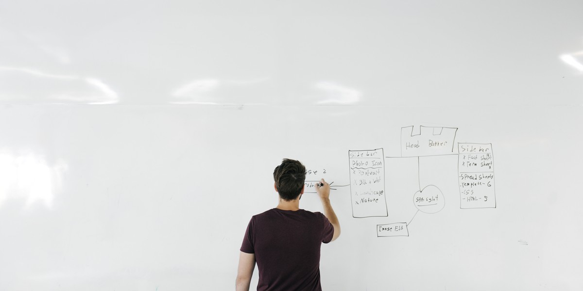 A man working on information architecture against a large whiteboard