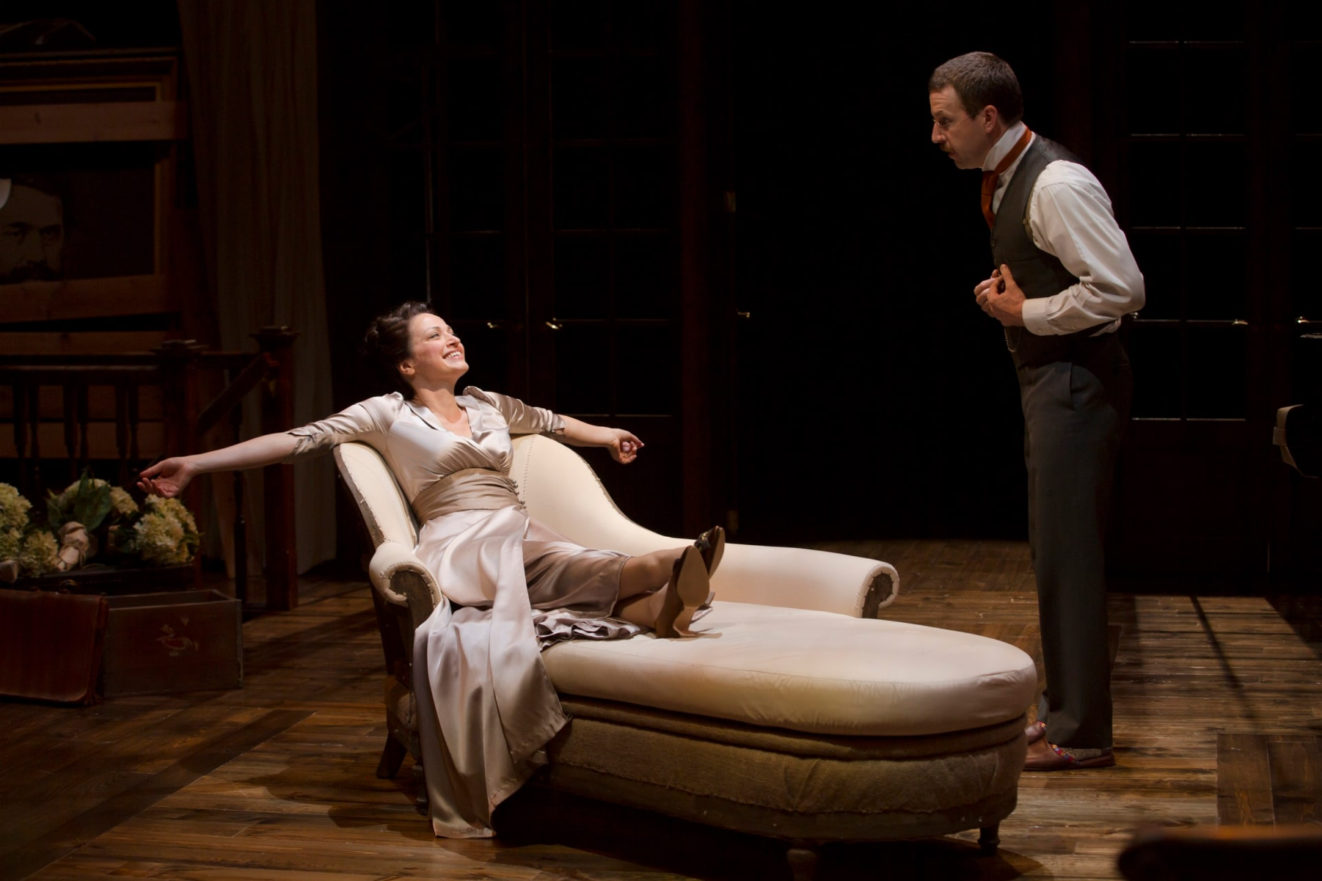 Woman in white silk gown lounges laughing on chaise with man in waistcoat standing beside.