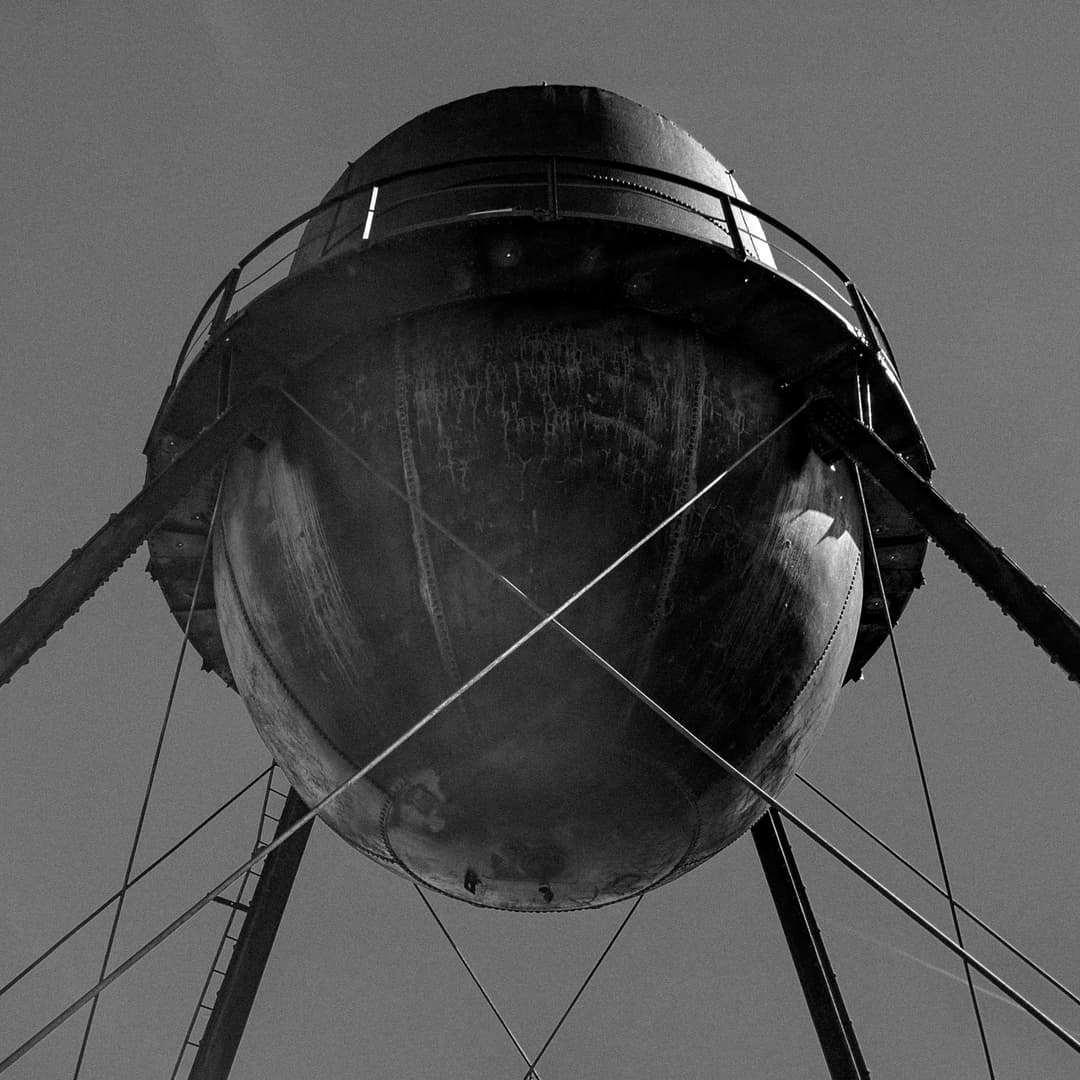 A black-and-white photo of an old steel water tower.