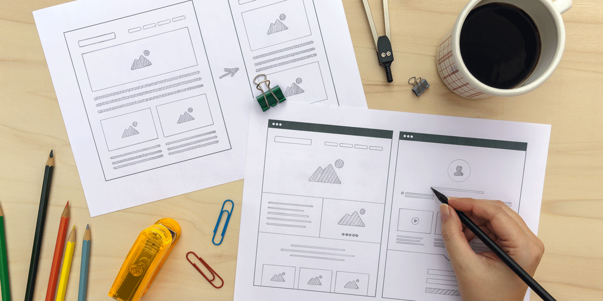 The hand of a designer drawing a wireframe using pen and paper on a table