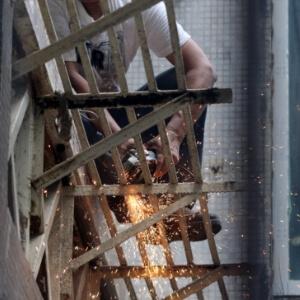 Homem serrando uma estrutura de metal.