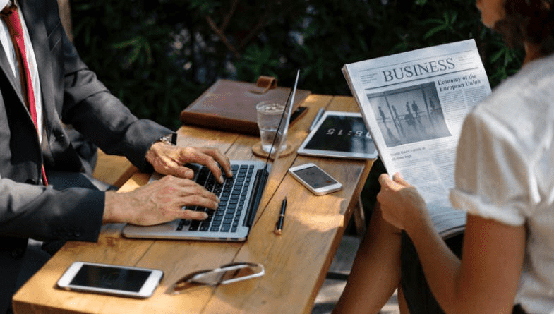 A man in a grey suit typing on a MacBook laptop opposite a woman in a white shirt reading the financial section of a newspaper.