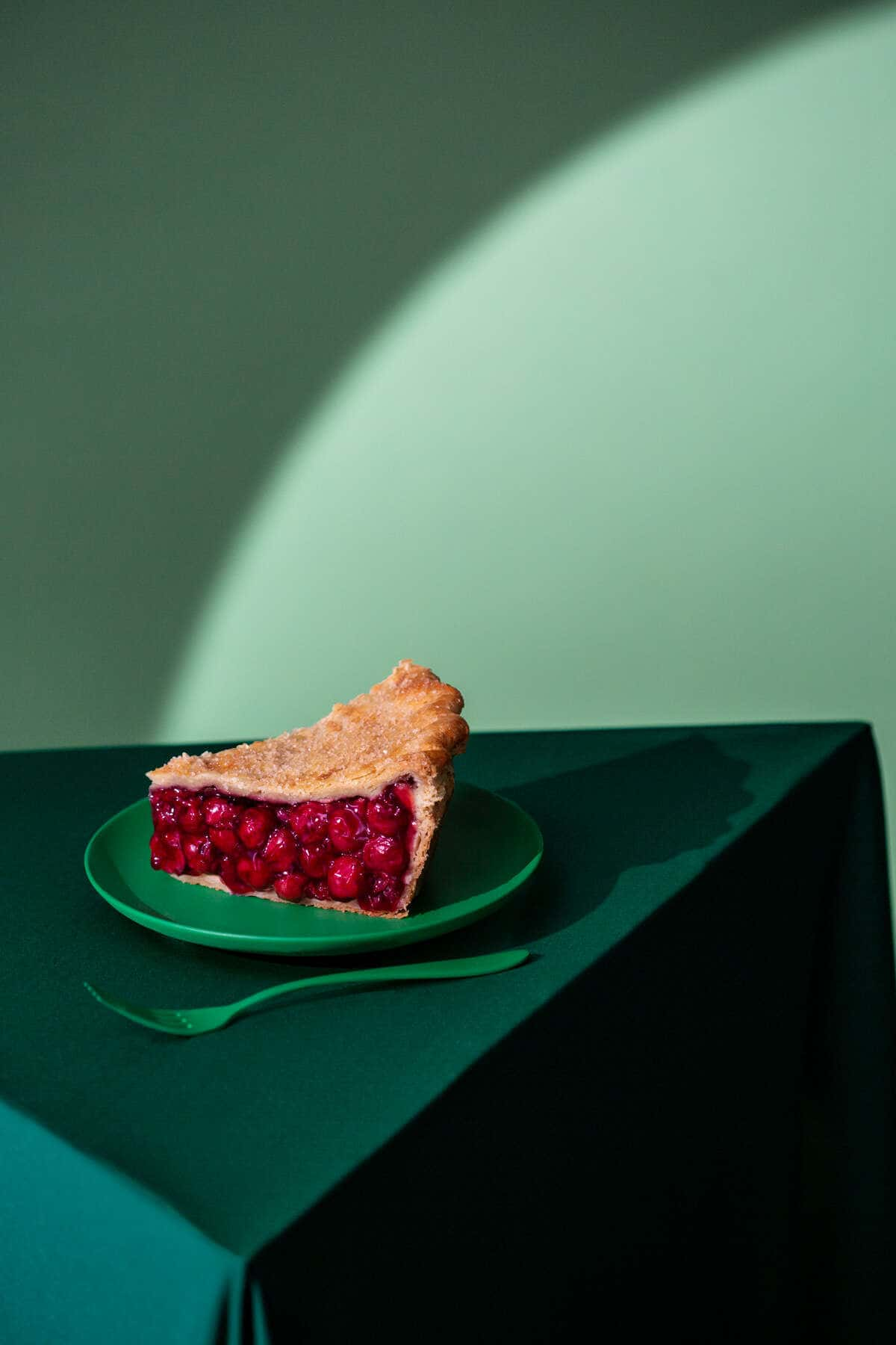 Cherry Pie sat on a green plate on a green table with a hard spotlight used to light the set