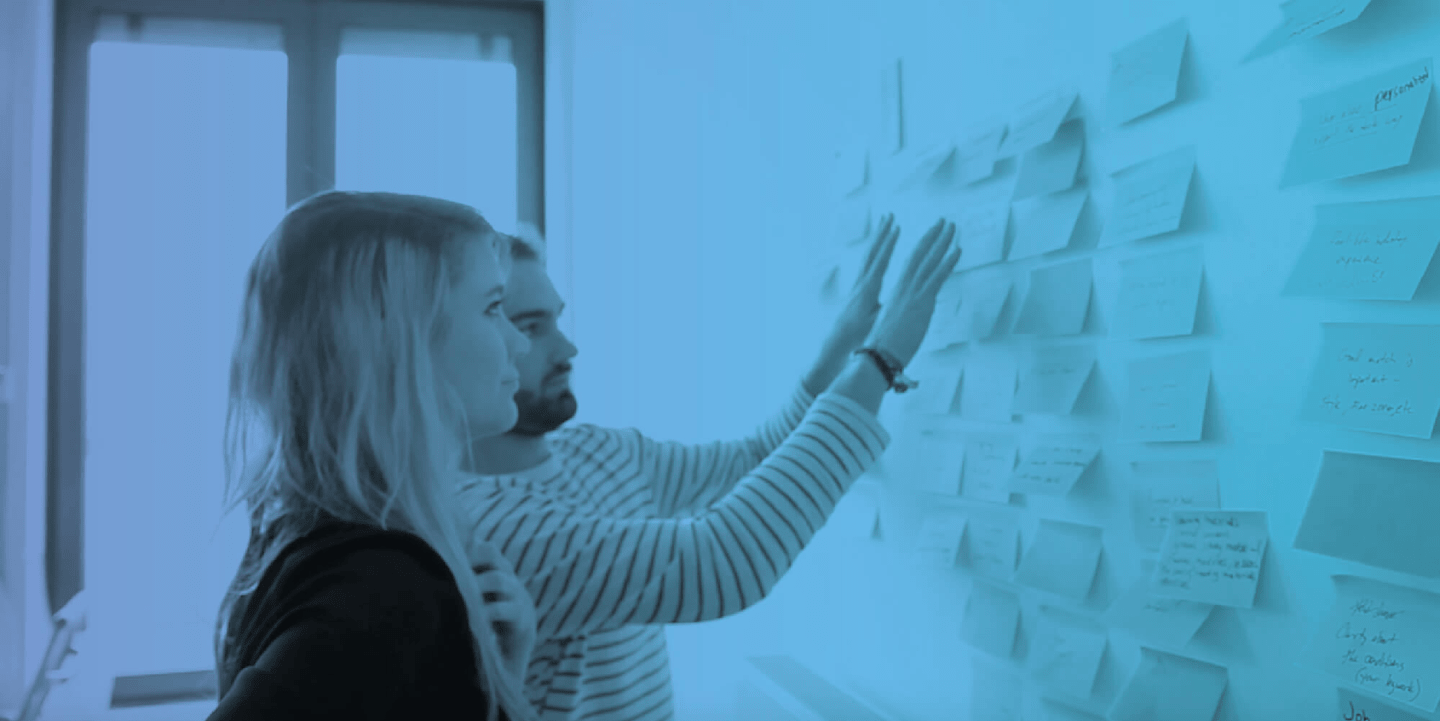 Two UX designers collaborating on a whiteboard