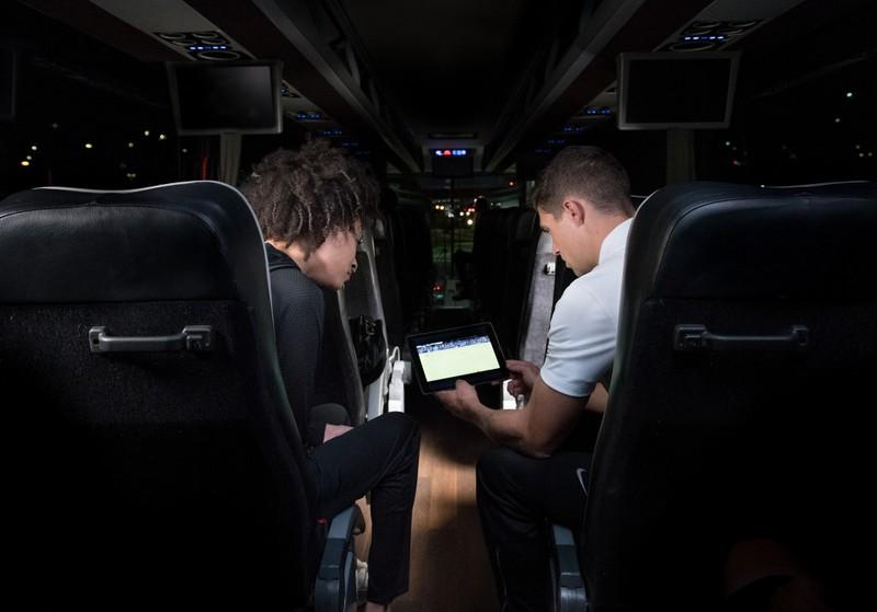 バスでサッカーの映像を見ている 2 人の男性