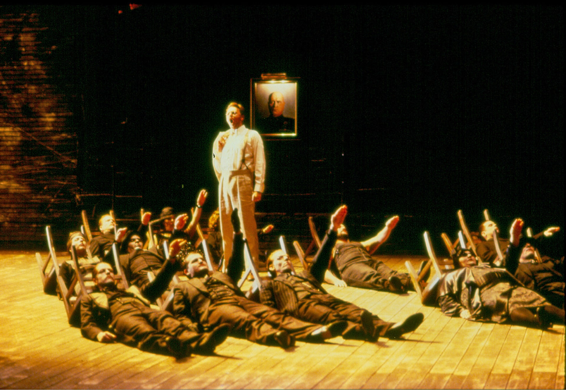 Man in white sings in front of portrait of Mussolini, surrounded by dark-suited men lying on bare wooden floor giving Nazi salute.