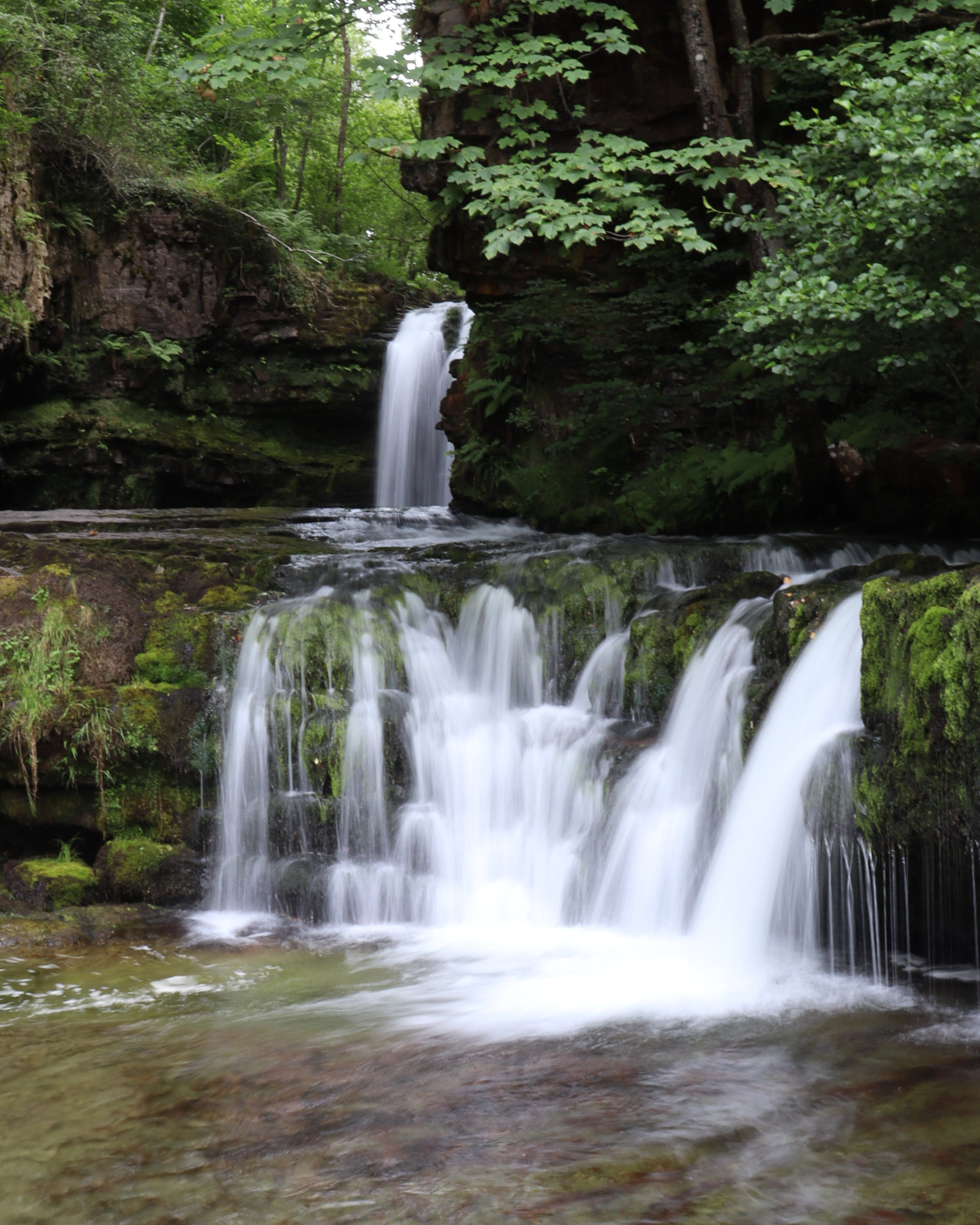 Long exposure shot of a waterfall in the distance feeding into a smaller drop in the foreground.