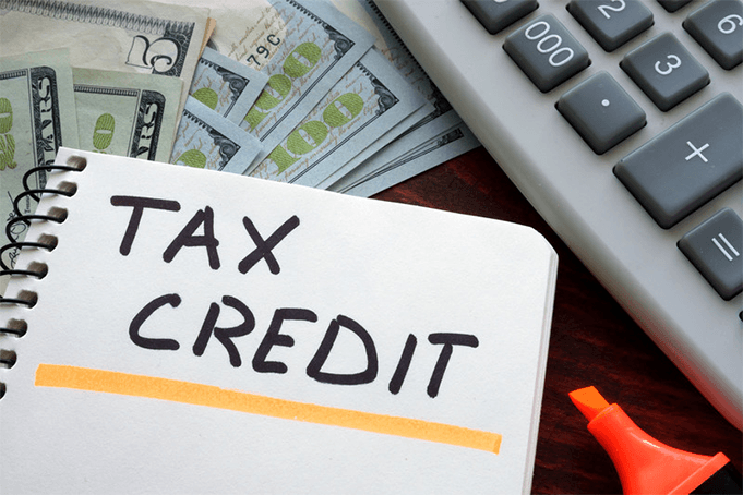 Tax credit written on a notepad in front of dollars and a calculator