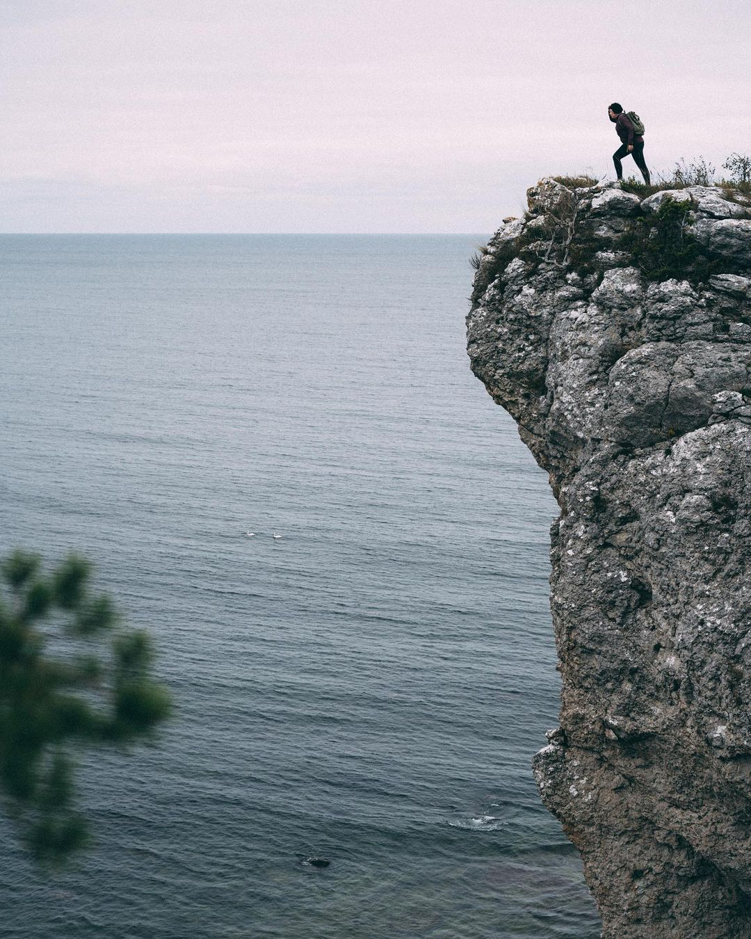A woman is standing at the edge of a cliff. Down below, the wind ruffles the water. The sky is overcast.