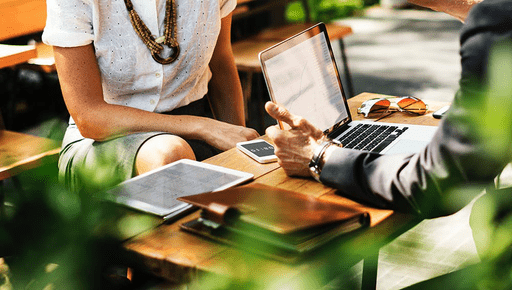 A woman and a man sitting at a table in the sunshine outside having a meeting using Futrli dashboards in office wear ands to make sure their businesses are performing well plants in the foreground.